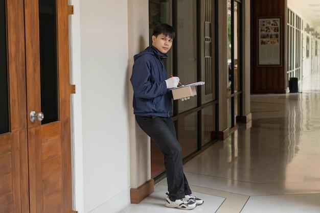 Paketzustellungskonzept der postbote in der blauen jacke überprüft die liste und den nächsten ort, um das paket zuzustellen.