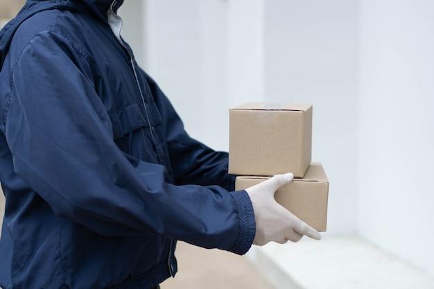 Paketzustellungskonzept der postbote in weißen gummihandschuhen und leichtem dunkelblauem mantel wartet darauf, seinem kunden vor dem gebäude kleine pakete zu übergeben.