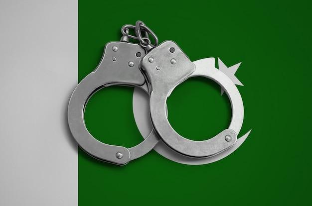Pakistan flagge und polizei handschellen. das konzept der einhaltung des gesetzes im land und des verbrechensschutzes