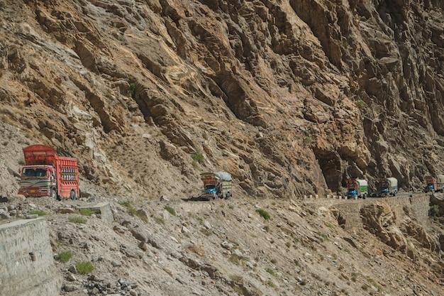 Pakistanische lkws, die auf gepflasterter straße entlang dem berg nahe der klippe in karakoram-landstraße reisen.