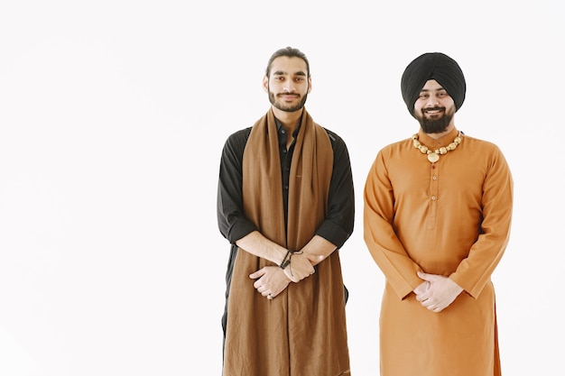 Pakistanischer mann und indische männer in traditioneller kleidung. die freunde sprechen auf weißem hintergrund, isoliert. abkommen zwischen den ländern.