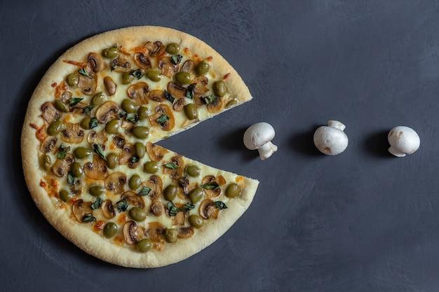 Pakman pizza mit pilzen und oliven auf einem schwarzen