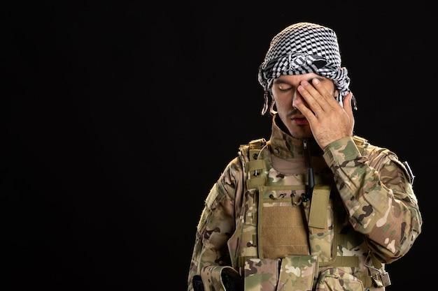 Palästinensischer soldat in militäruniform an dunkler wand
