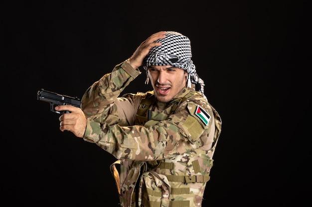 Palästinensischer soldat in tarnung mit pistole an einer schwarzen wand
