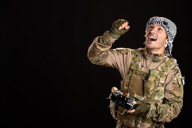 Palästinensischer soldat mit fernbedienung an schwarzer wand