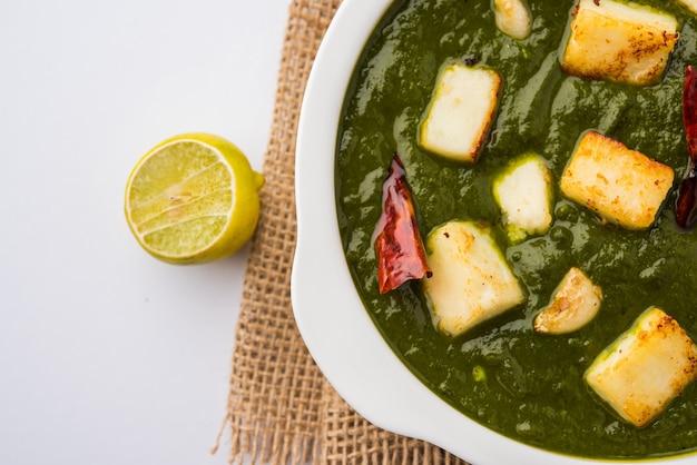 Palak paneer curry aus spinat und hüttenkäse, beliebtes indisches gesundes mittag- oder abendessen, serviert in einem karahi mit roti oder chapati über stimmungsvollem hintergrund. selektiver fokus