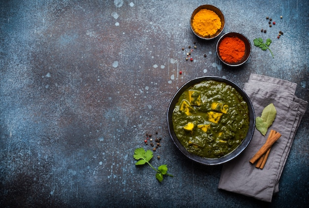 Palak paneer, traditionelles vegetarisches indisches gericht mit käsepaneer, püriertem spinat und gewürzen. indischer grüner paneer in rustikaler keramikschale auf betonhintergrund, draufsicht und platz für text