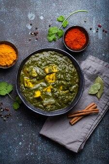 Palak paneer, traditionelles vegetarisches indisches gericht mit käsepaneer, püriertem spinat und gewürzen. indisches grünes paneer-curry in rustikaler keramikschale auf betonhintergrund, ansicht von oben