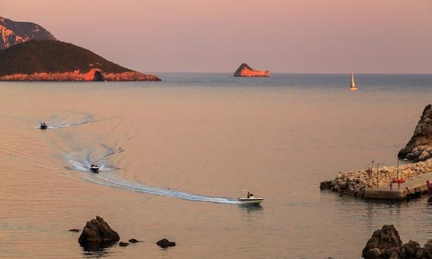 Paleokastritsa korfu griechenland sonnenuntergang licht spiegelt sich im meer schwimmende segelboote sommer