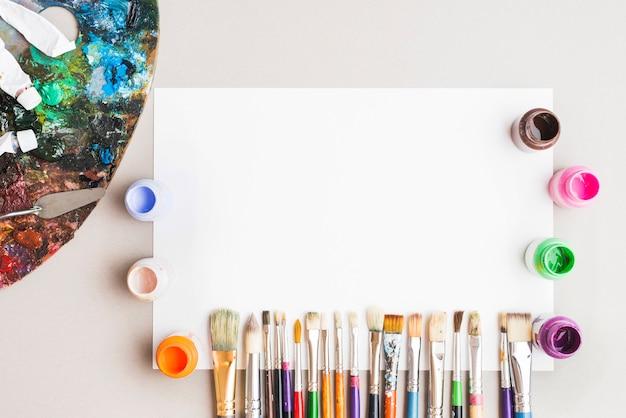Palette in der nähe von kunstbedarf und leeres papier
