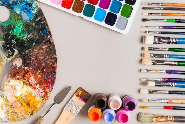 Palette in der nähe von pinseln und farben
