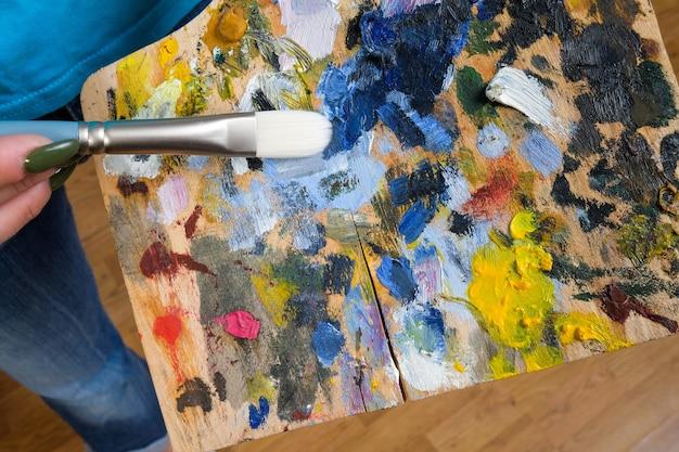 Palette mit farben und pinsel auf dem tisch