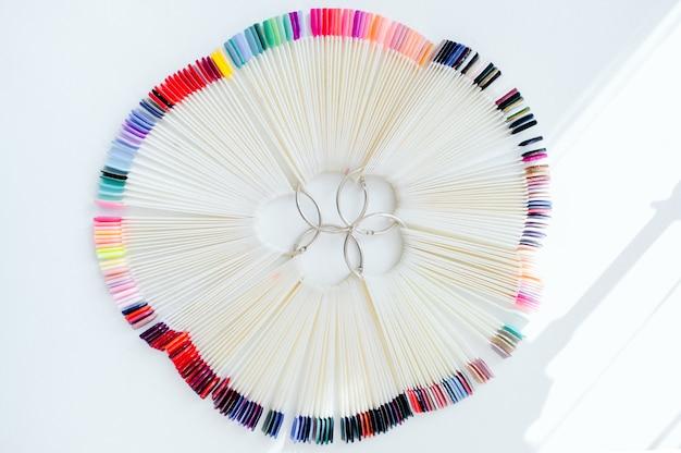 Palette mit farbfeldern des nagellacks. eine sammlung von lackproben für die maniküre. gepflegte hände, gesunde nägel. selektiver fokus. große auswahl an leuchtenden farben