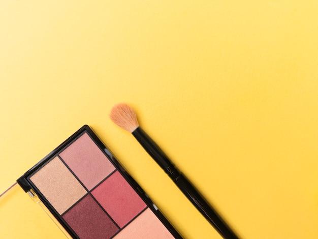 Palette und pinsel auf gelbem thema bilden rahmen für förderung.