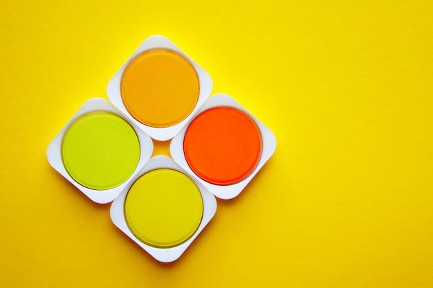 Palette von gelb- und orangetönen von aquarellfarben auf einem gelb Premium Fotos