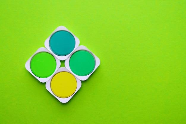 Palette von grün-, türkis- und gelbtönen von aquarellfarben auf einem grünen hintergrund