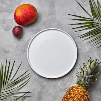 Palmblätter leeren weißen teller und eine reihe verschiedener tropischer früchte mango, passionsfrucht, ananas auf grauem betonhintergrund mit platz für text.