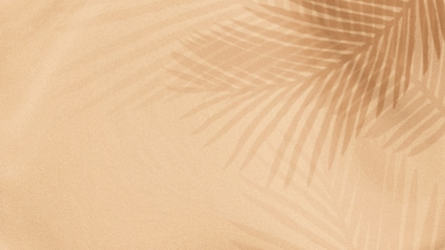 Palmblätter schatten auf einem beigen hintergrund