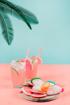 Palmblätter über den grapefruit-cocktailgläsern; eis am stiel auf korallenschreibtisch gegen aquamarinen hintergrund