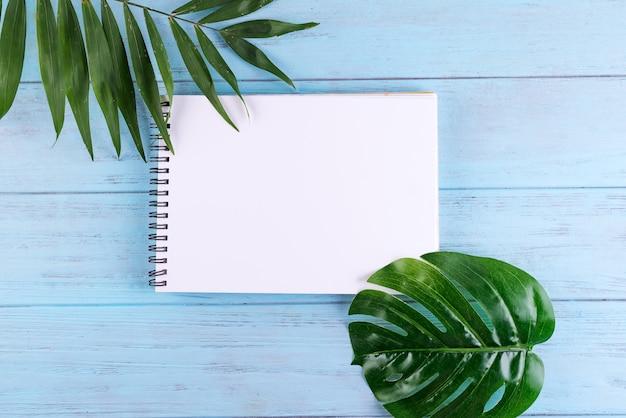 Palmblätter und ein papiernotizbuch mit freiem platz für text auf blauem hölzernem hintergrund.