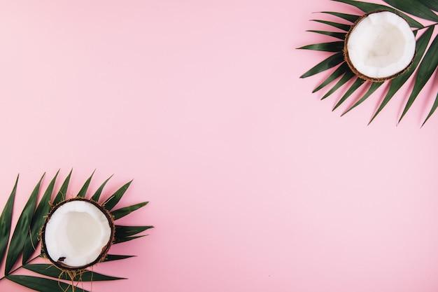 Palmblätter und kokosnüsse ganz und hälften der kokosnuss auf einem rosa pastellhintergrund.