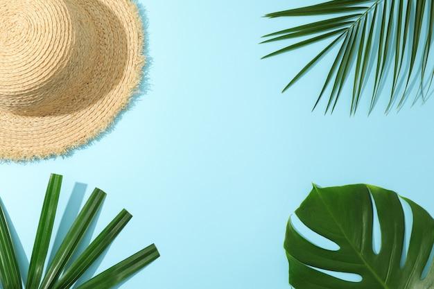 Palmblätter und strohhut auf blauem tisch