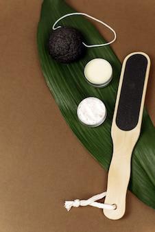 Palmblatt mit natürlichem verschiedenen bimsstein zum peeling der haut liegt auf einem braunen hintergrund mit kopierraum. das konzept, die haut der füße mit einer creme, lotion oder balsam zu befeuchten