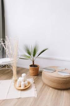 Palme in einem topf und rattan dekorationselemente. umweltfreundliche innenarchitektur des wohnzimmers im modernen haus.