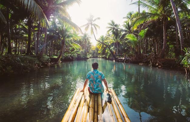 Palmen-dschungel auf den philippinen. konzept über fernweh tropische reisen. auf dem fluss schwingen. leute, die spaß haben