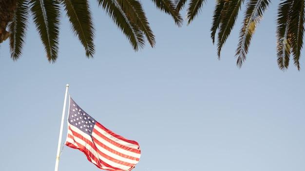 Palmen und amerikanische flagge, los angeles, kalifornien usa. sommerästhetik von santa monica und venice beach. sternenbanner, sternenbanner. atmosphäre des patriotismus in hollywood. alter ruhm