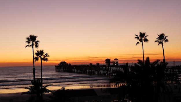 Palmen und dämmerungshimmel in kalifornien usa. tropische ozeanstrand-sonnenuntergang-atmosphäre. los angeles-vibes.