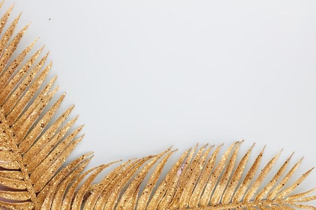 Palmgoldblatt auf blauem hintergrund. palmblatt, flache lage und draufsicht.
