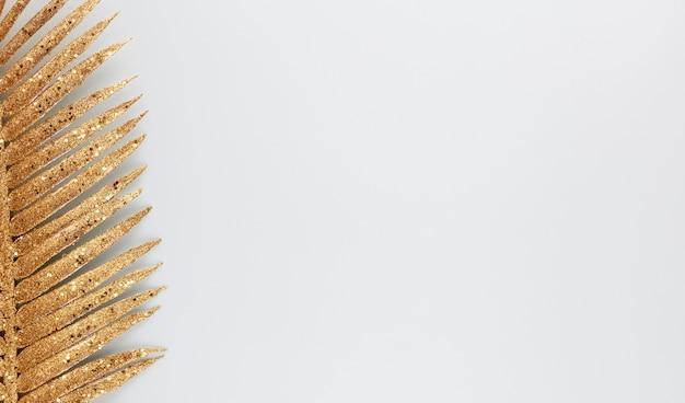 Palmgoldblatt auf blauem hintergrund.