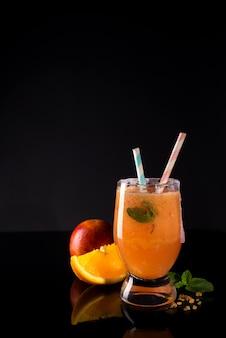 Paloma-cocktail mit frischer pampelmuse, orange und minze auf einem schwarzen glashintergrund