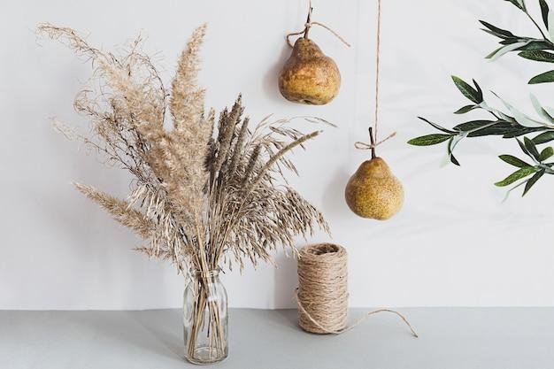 Pampasgras in einer glasvase und birnen