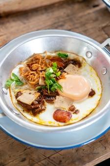 Pan fried egg topping mit thailändischer wurst auf holztisch