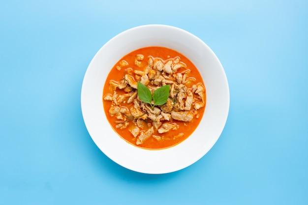 Panaeng curry mit huhn in der weißen schüssel auf blauem hintergrund.