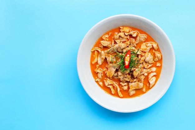 Panaeng curry mit schweinefleisch in weißer schüssel auf blauer oberfläche.
