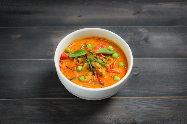 Panaeng curry mit schweinefleisch oder rotes curry mit schweinefleisch (panang schweinefleisch) auf holztisch