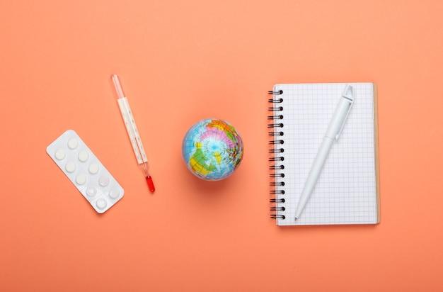 Pandemie-ausbruch oder konzept der globalen erwärmung. globus, thermometer, notizbuch und pillenblase auf orangefarbenem hintergrund. draufsicht