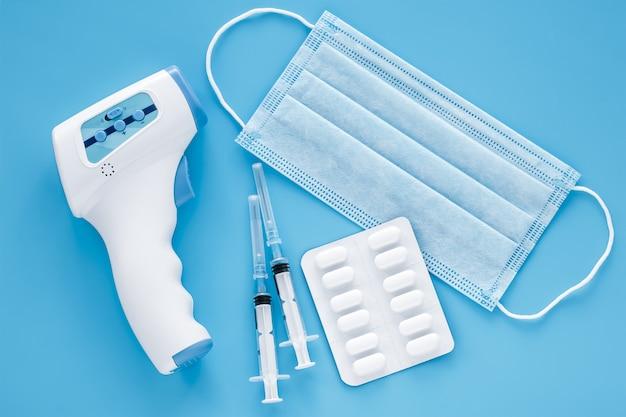 Pandemie des coronavirus (covid-19). chirurgische schutzmaske, pillen, elektronisches infrarot-thermometer und zwei spritzen auf blau. konzept der medizin, quarantäne