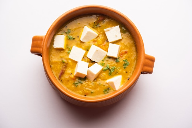 Paneer dal fry ist eine kombination aus hüttenkäsewürfeln, die in gelbe linsenmasala getaucht werden. in einer schüssel serviert