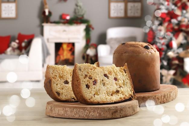 Panettone scheibe mit kandierten früchten zu hause mit weihnachtsdekoration im hintergrund.