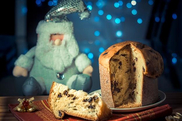 Panettone. traditioneller italienischer nachtisch für weihnachten mit chistimas beleuchten auf hintergrund