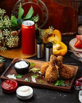 Panierte hähnchenschenkel serviert mit saucen