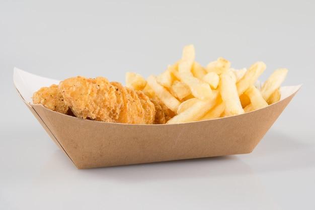 Panierte hähnchenstreifen mit pommes frites und dip im karton