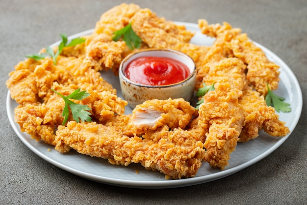 Panierte hühnerstreifen mit saucen.