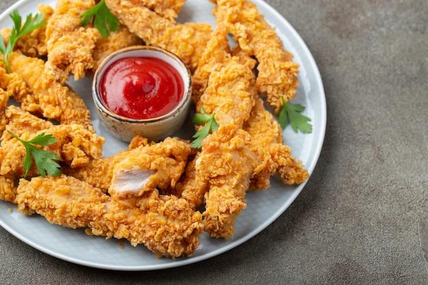 Panierte hühnerstreifen mit zwei saucen.