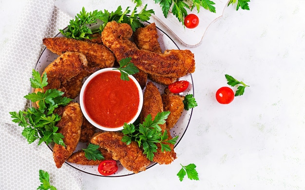 Panierte mini-hähnchenfilets mit tomatensauce. amerikanisches essen. hühnernuggets mit petersilie. draufsicht, kopierraum