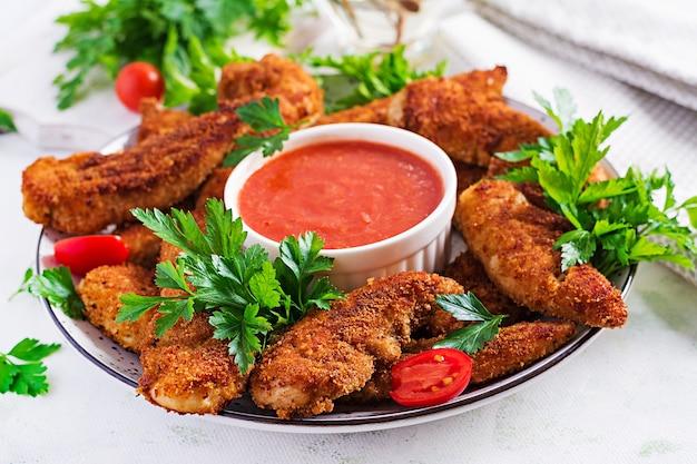Panierte mini-hähnchenfilets mit tomatensauce. amerikanisches essen. hühnernuggets mit petersilie.